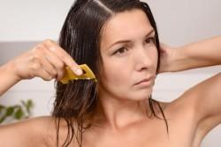 Frau kämmt aus ihren Haaren Kopfläuse aus.