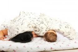 Mutter und Baby schlafen unter einer Bettdecke