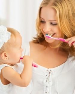 Mutter und Baby üben gemeinsam das Zähneputzen