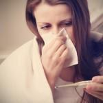 kranke Mutter putzt sich die Nase und misst Fieber
