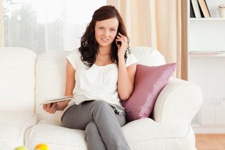 Schwangere Frau telefoniert, um eine Hebamme zu finden