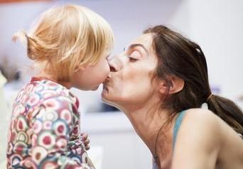 Lippenkuss zwischen Mutter und Tochter
