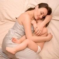 Mutter stillt ihr Kleinkind im Bett