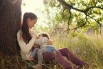 Junge Mutter stillt ihre vierjährige Tochter im Freien unter einem Baum