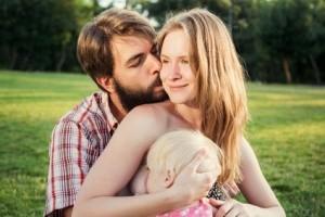 Vater küsst seine Frau, während diese die kleine Tochter stillt.