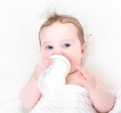 Baby bringt sich mit der Flasche in den Schlaf.