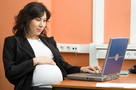 Schwangere Frau sitzt vor dem Laptop und informiert sich über das Stillen
