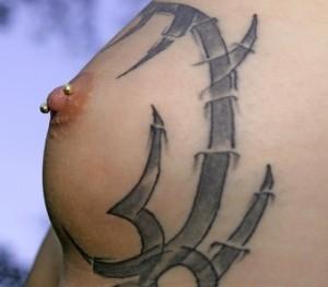 Brust mit Piercing und Tatoo