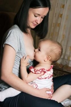 Mutter stillt ihr Baby im Hoppe-Reiter-Sitz