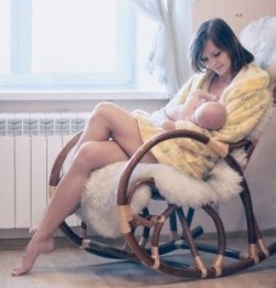 Mutter still ihr Baby im Schaukelstuhl