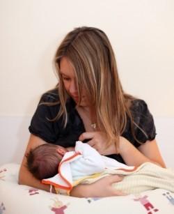 Mutter stillt ihr Baby in der Wiegenhaltung