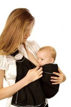 Mutter stillt ihr Baby in einer Babytrage