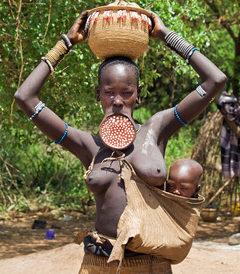 Afrikanische Mutter mit Baby im Tragesack vor der nackten Brust