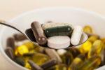 Tabletten und Pillen auf einem Löffel und in einer Schüssel