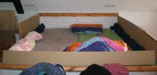 Ehebett mit Möbelkartons als Gitter