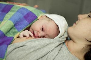 Neugeborenes Baby auf der Brust der Mutter unter einer dicken Decke