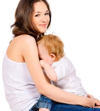 Kleinkind trinkt an der Brust der lächelnden Mama