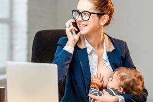 Mutter stillt vor dem Computer und mit Telefon in der Hand
