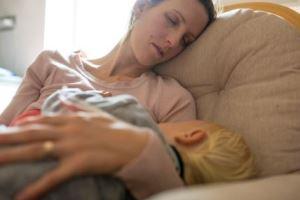 Erschöpfte Mutter mit Kleinkind an der Brust