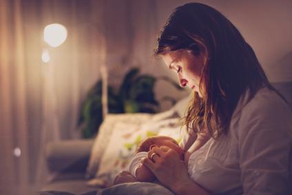 Mutter stillt ihr Baby im Sitzen nachts