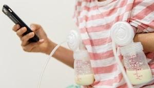 Frau beim Abpumpen von Muttermilch und Handy in der Hand