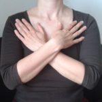 Oberkörper einer Frau mit überkreuzten Händen