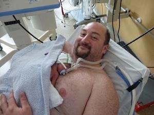 Vater mit Frühgeborenem Baby auf Intensivstation in Haut-zu-Haut-Kontakt