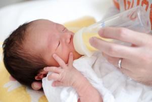Frühgeborenes Baby wird mit Flasche gefüttert.