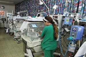 Inkubatoren und Wärmebetten aneinandergereiht, nur mit einer Pflegekraft