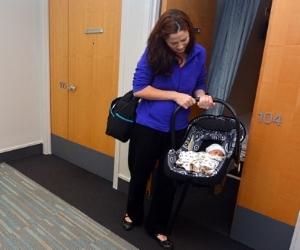 Mutter bringt ihr Baby in einem Autositz im Krankenhaus