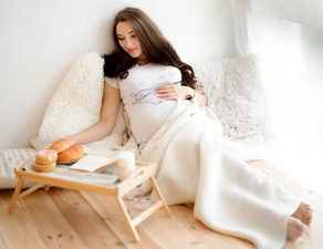schwangere Frau liegend am Fenster