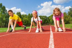 Drei kinder hocken in der Startposition zum Sprinten